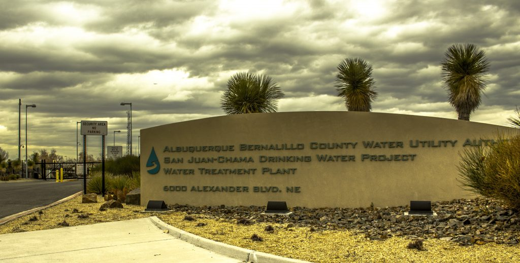 """""""water utility sign""""                             Photo by Evan Barela Water from the Rio Grande is diverted to a $160 million Water Treatment Plant. The Plant, with a capacity of roughly 80 million gallons per day, employs both mechanical and chemical processes to remove contaminants from the water."""