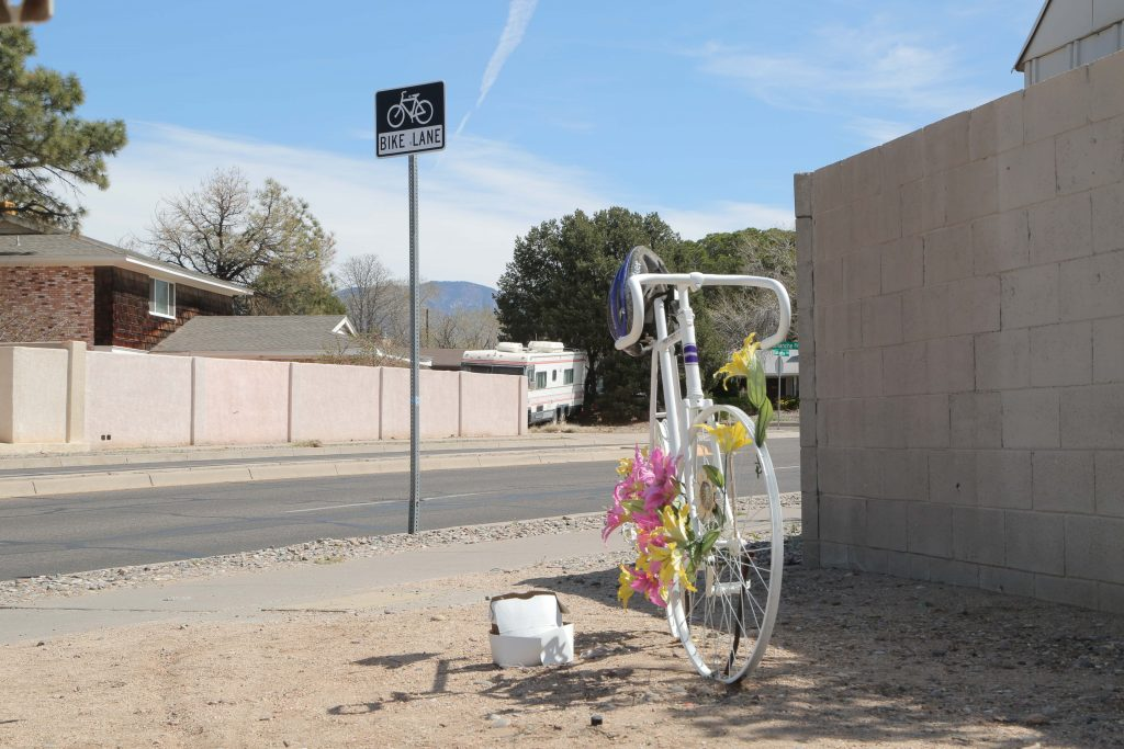 Paula Higgins, who passed away in 2006 while riding her bike on Comanche Road near Pennsylvania Street, has a ghost bike set up in her remembrance. Comanche Road includes one of the longest bike lanes in Albuquerque, N.M. Photo by Jaclyn Younger / NMNP