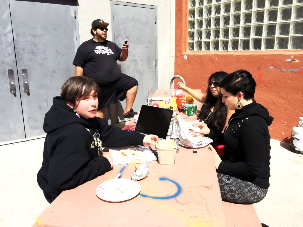 """Warehouse 508 staff (from left to right) April Freeman, """"Berto"""" Roberto Reyes, Ruby Rodriguez and UNM intern Keara Dayton share BBQ pork ribs and potatoes on the patio on a recent day. Photo by Mercedez Holtry/ NM News Port"""
