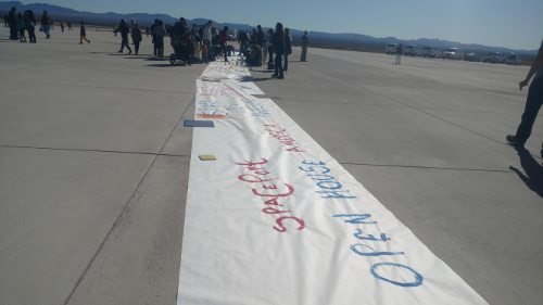 Children decorate a banner commemorating the Spaceport's second biannual open house. Photo by Marissa Higdon / NM News Port.