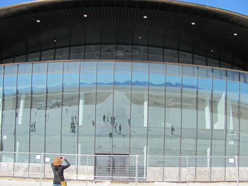 The image of surrounding mountains is reflected in the windows of the spaceport. Photo by Marissa Higdon / NM News Port