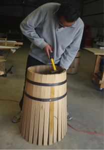 Mahad Ahmed, co-owner of D.R. Cooperage and Grain works on shaping an American white oak barrel inside the shop located on Isleta Pueblo. Photo by Alicia Padilla / NM News Port.