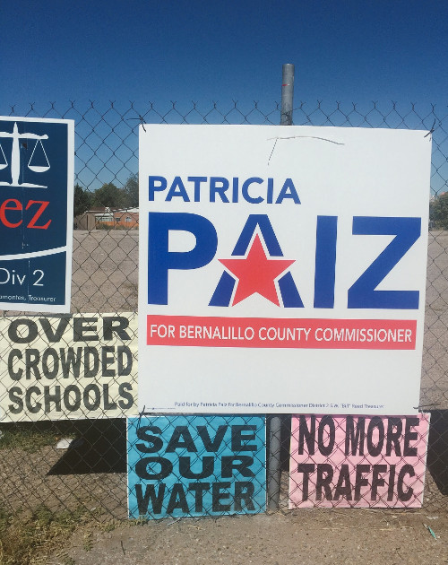Protest signs surrounding a Patricia Paiz campaign sign on Bride Blvd. These signs reference how the Santolina Master Plan would allegedly stretch South Valley resources thin. Photo by Christina Rodriguez / NM News Port